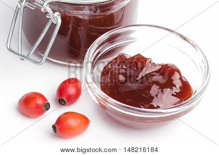 Rose hip jam and fruits from above over white, also rose haw or rose hep. Marmelade in glass jar and bowl. Shells of red fruits can be eaten raw and are one of the richest vitamin C sources in plants.