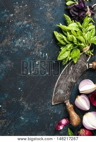 Healthy food cooking background. Fresh green and purple basil leaves, red onions and garlic with herb chopper knife over grunge dark blue painted plywood texture. Top view, copy space