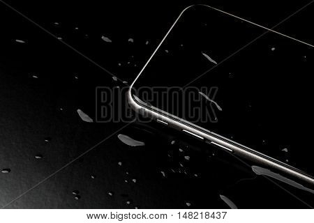 Waterproof smartphone with splashing of water on black  background