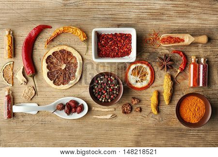 Flat lay of assorted herbs and spices on wooden background