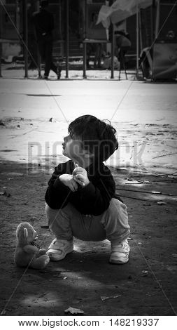 SERBIA BELGRADE - September 14 2015: Park at the station migrants from Syria have turned into a small city. Child in the dirt with teddy bear. Some have even set up tents and in which they reside while most sleep under the open sky.