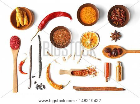 Flat lay of assorted herbs and spices on white background