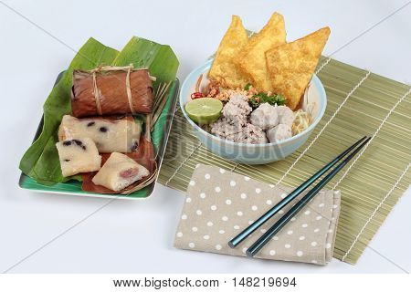 Crispy noodle in spicy sour soup and  streamed sticky rice and black bean  in banana leaf  on white background. Side view.