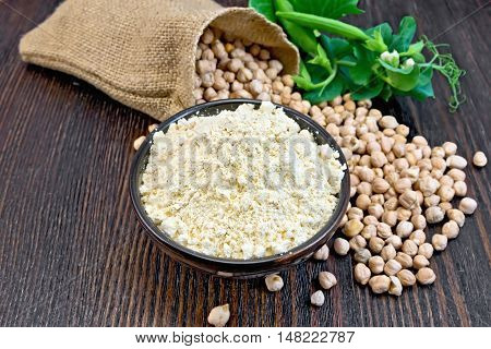 Flour chickpeas in a bowl, chick-peas in a sack and fresh pea pods on a background of dark wood planks
