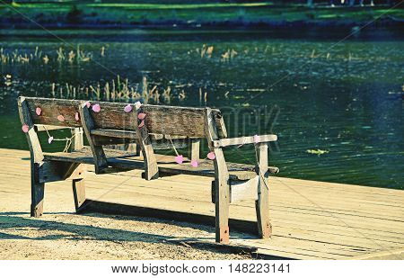 Rustic wooden park bench draped in faded pink party decorations on the bank of an emerald green river. Audley, Royal National Park, Australia