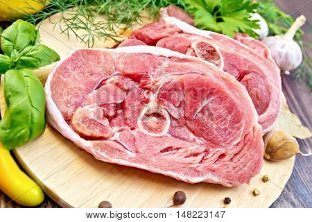 Steak meat raw turkey with pepper, basil, lemon and garlic on a wooden boards background