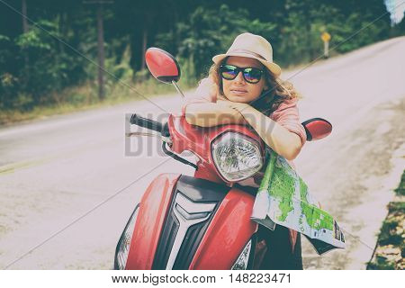 Young woman traveller on the road in tropical jungle on motorbike. Vacation and adventure concept.
