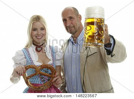 Woman in Dirndl with pretzel and Man with Beer Mug in traditional Oktoberfest clothing