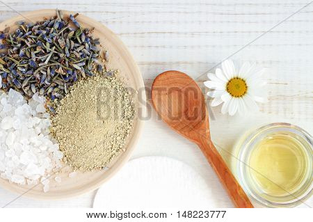 Cosmetic herbal ingredients for homemade spa skincare. Mix of sea salt, lavender, bentonite clay, oil, chamomile.  Holistic Skincare preparation background. Fancy spa facial at home.