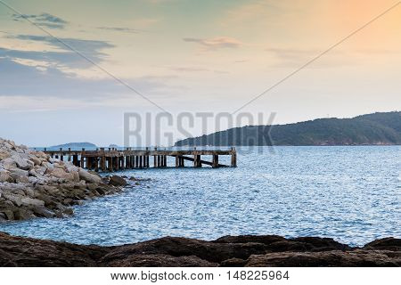 Old concrete jetty before sunset. Evening sea view with rocks and islands in background.