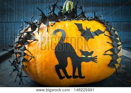 Idea homemade decorating for Halloween. Application: barbed tape made of black crepe paper and cat on pumpkin. The original design in the style of Halloween. Tinted photo