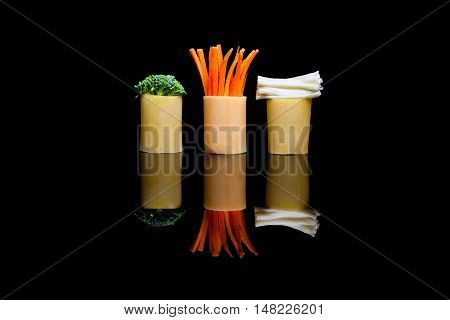 Three pieces of pasta with embedded red carrots green broccoli and white cheese on a black reflection background