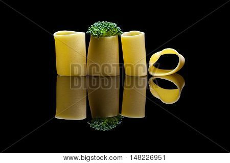 Broccoli embedded into pasta on a black reflection backround
