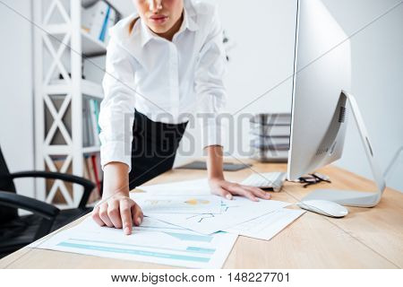 Cropped image of smart serious businesswoman pointing finger at work documents on the table in office