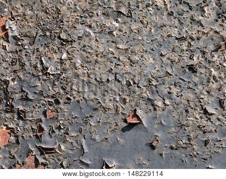 Black peeling paint on a rusty surface.