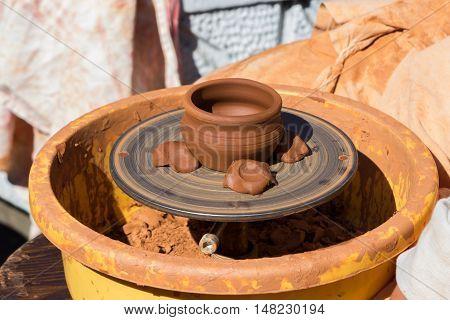 Process of ceramic jug creation on a turning wheel. Handmade crockery made by potter.