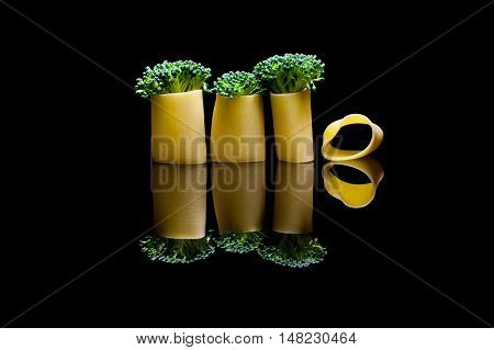A group of three broccoli embedded into pasta manicotti on a black reflection backround