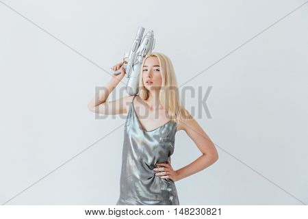 Young beautiful fashion blonde woman holding blaster and posing isolated on the grey background
