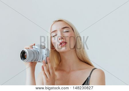 Close up potrait of a beautiful young girl with eyes closed holding camera isolated on the grey background