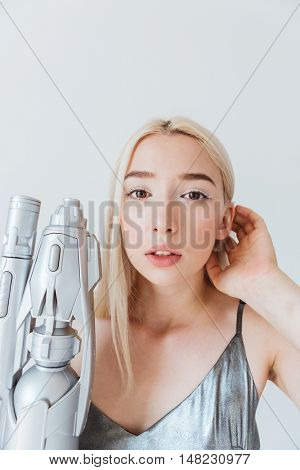 Close up portrait of a beautiful fashion blonde in silver shiny dress holding blaster isolated on the grey background
