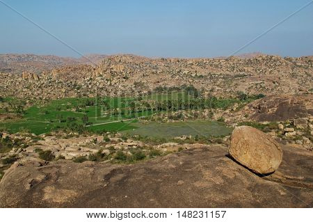 Unique landscape in Hampi India. Rice fields in surrounded by granite mountains.