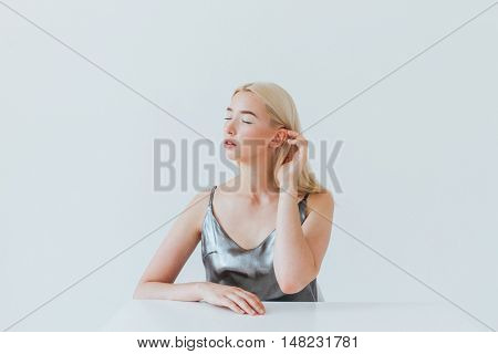 Beauty portrait of a young blonde girl with eyes closed sitting at the white table isolated on the grey background
