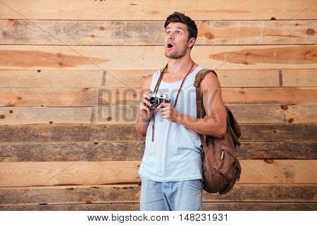 Surprised man tourist with backpack holding retro camera isolated on a wooden background