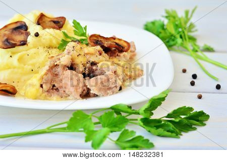 Pepper, twigs of parsley on a wooden table next to a white plate with mashed potatoes, meat and mushrooms