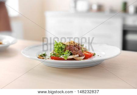 Plate with salad and tomato sauce on table on blurred kitchen background
