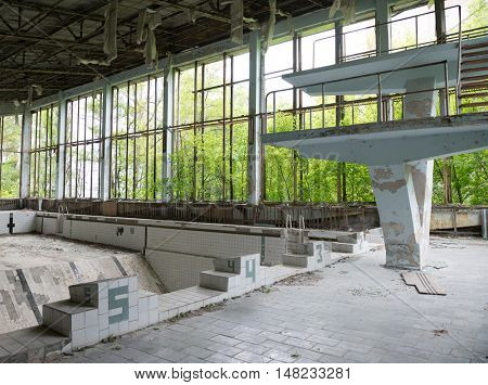 gym with swimming pool and debris in abandoned Sports Palace in Pripyat