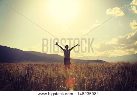 cheering young woman open arms on grassland