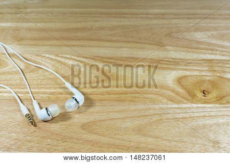 Closeup headphone or earphone  on wooden background.