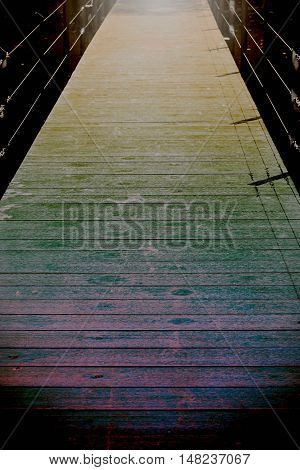 Wooden bridge walkway with light and darkness.