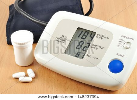 Digital blood pressure monitor with tablets on the table