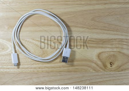 USB cable power adapter on wooden background.