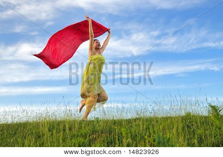 beautiful young and healthy woman run and jump on meadow at sunny day with red scarf