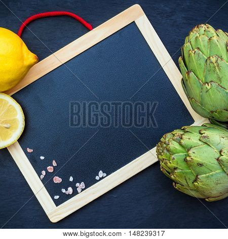 Organic fresh artichokes with lemon with copy space board, grunge moody background. Selective focus, top view overhead flat lay