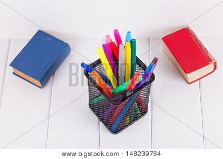 Multicolored markers in the stand next to small books on a white background