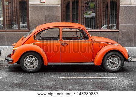 BUDAPEST, SEPTEMBER 17: Orange retro car Volkswagen Beetle parked on the old street on September 17, 2016 in Budapest, Hungary.