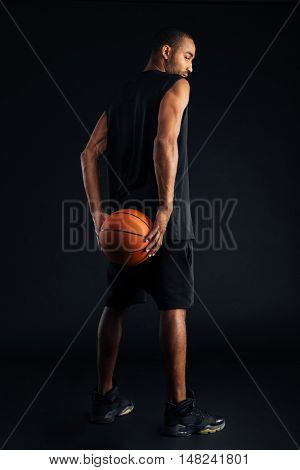 Back view portrait of an african basketball player standing isolated on a black background