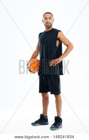 Full length portrait of a handsome basketball player standing isolated on a white background
