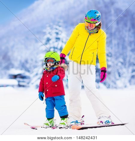 Mother and little child skiing in Alps mountains. Active mom and toddler kid with safety helmet goggles and poles. Ski lesson for young children. Winter sport for family. Little skier racing in snow