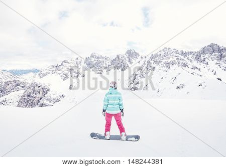 Female snowboarder wearing colorful helmet, blue jacket, grey gloves and pink pants standing against snowy mountains and preparing for ride - snowboarding concept