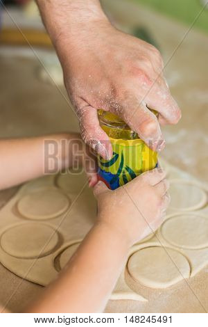 Children and dad cook hands the circles of dough