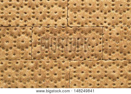 Crisp rye bran bread texture background with brickwork