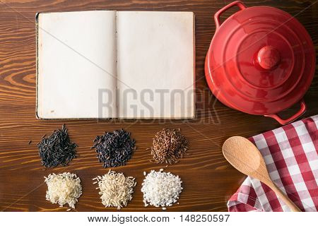Blank cookbook and different rice varieties. Top view.