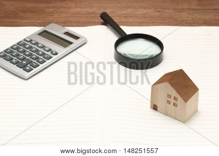 Miniature house, magnifying glass, calculator, and notebook. New house concept.