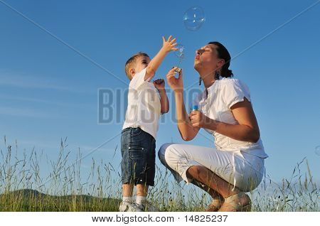 happy child and woman outdoor playing with soap bubble on meadow