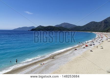 OLUDENIZ TURKEY - JUNE 04: Tourists visit Oludeniz beach in Turkey on JUNE 04 2016. Oludeniz beach is one of the best beaches in Turkey it's situated on Mediterranean Sea