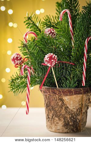 Red cake pops with ribbon in Christmas decoration bouquet with candy canes and some spruce. Very shallow depth of field and Christmas lights in the background